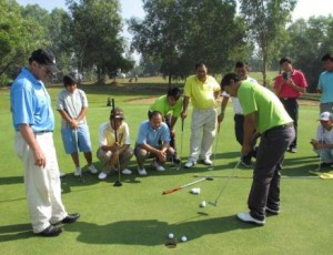 Mark Holland (left) conducts a putting clinic in Myanmar.