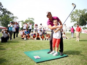 Liang Wenchong introduces a Hong Kong youngster to golf.