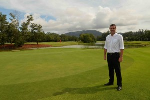 Laguna Phuket's Director of Golf Paul Wilson beside the eighth green with Phuket's iconic mountains in the background.