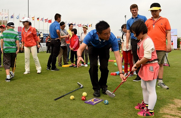 Mission Hills Academies professional Jason Wu coaches a youngster during the children's clinic at the World Ladies Championship. Picture by Khalid Redza for Mission Hills