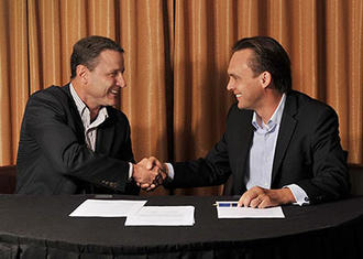 Senninger President James Burks and Greg Hunter, CEO at Hunter, make the acquisition official.