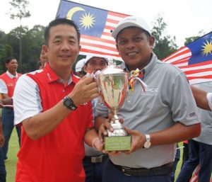 Singapore captain Thomas Leow (left) hands over the Causeway Cup trophy to his Malaysian counterpart Jonathan Ponniah.