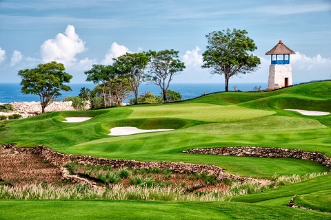 The 148-yard 13th is framed by three bunkers and features curved stone walls in the foreground and a traditional Balinese kul-kul tower in the background.